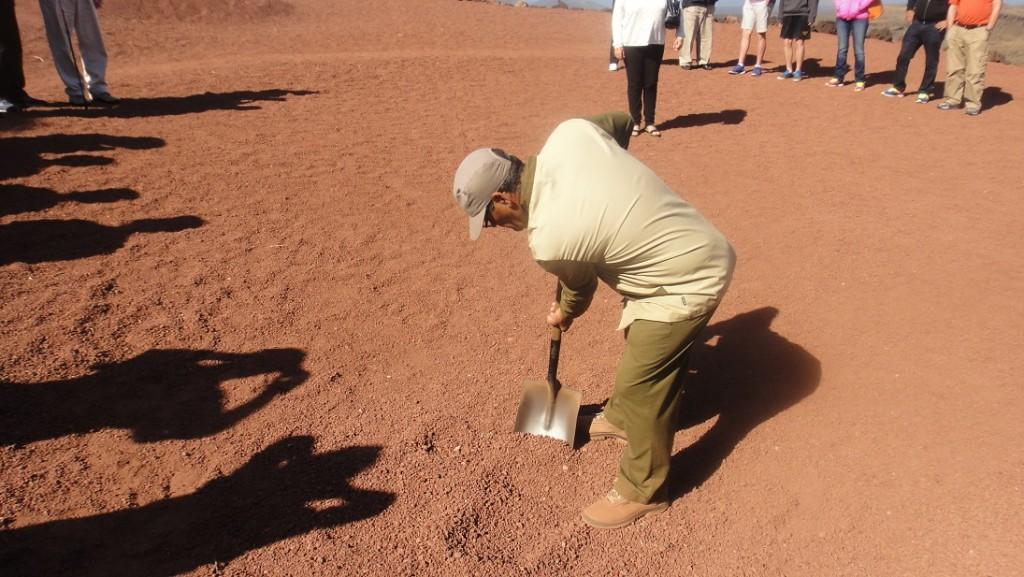 工作人員鏟起地上的砂礫,放一點在大家的手上